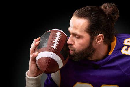 American football player kisses the ball Stock Photo