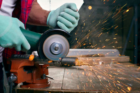 Gloved hands hold an angle grinder and cut the pipe, many sparks fly to the sides