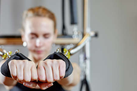 gym woman pilates stretching sport in reformer bed instructor girl. Selective focus on hands