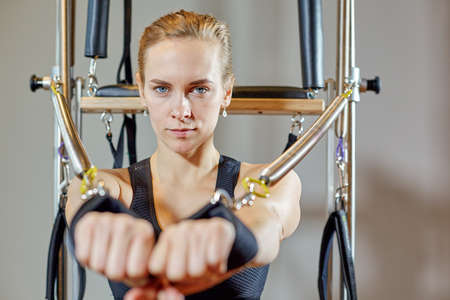 gym woman pilates stretching sport in reformer bed instructor girl. Selective focus on hands Stock Photo