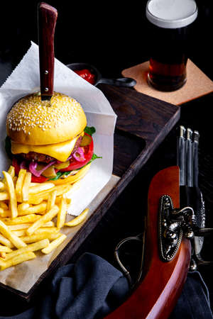 Craft beef burger and french fries on table in restaurant with glass of beer on dark background. Modern fast food lunch frame Banque d'images - 119238160