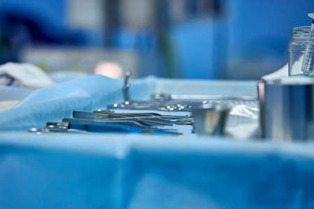selective focus surgical instrument lying on table, emergency case, surgery, medical technology, health care cancer, disease treatment concept