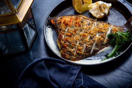 Flounder fillet roasted in a skillet with herbs and lemon Standard-Bild