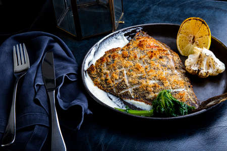 Flounder fillet roasted in a skillet with herbs and lemon 免版税图像