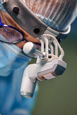 Close up portrait of female surgeon doctor wearing protective mask and hat during the operation. Healthcare, medical education, surgery concept. Stock Photo