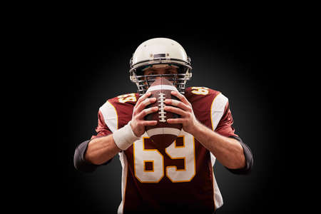 Portrait of American football player holding a ball with both his hands Imagens