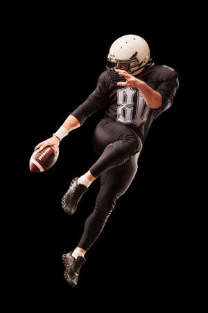 American football player in a jump with a ball on a black background