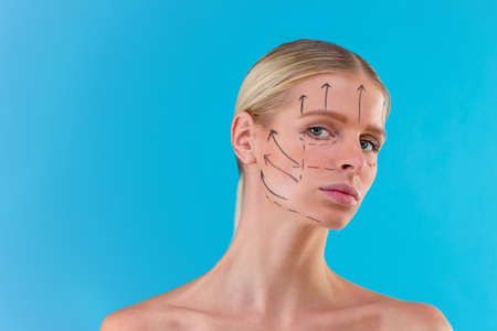 Beautician draw correction lines on woman face. Before plastic surgery operetion. Isolated on blue Imagens