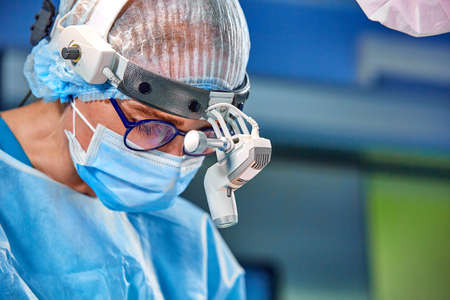 Close up portrait of female surgeon doctor wearing protective mask and hat during the operation. Healthcare, medical education, surgery concept. Imagens