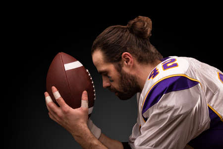 american football player with a ball On moment to pray before the game Standard-Bild