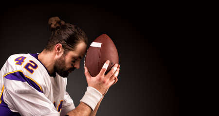american football player with a ball On moment to pray before the game Imagens
