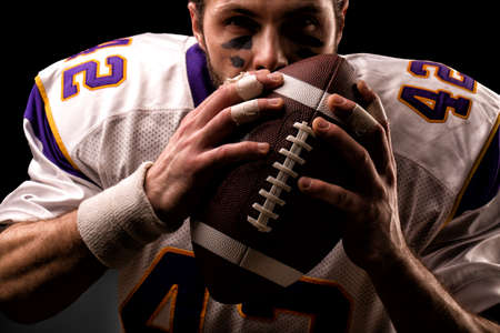 Close up portrait of American Football Player who gently kiss the ball