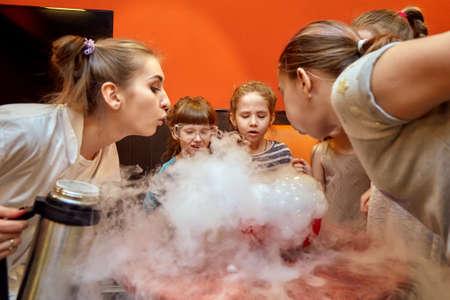 Espectáculo químico para niños. El profesor llevó a cabo experimentos químicos con nitrógeno líquido en cumpleañera.