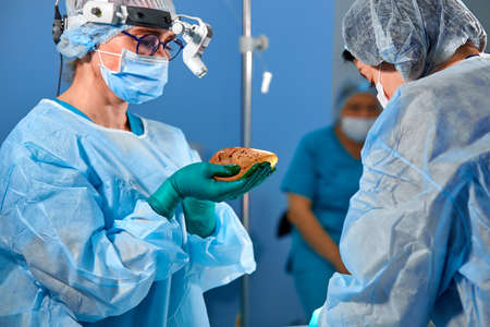 Surgeon performing cosmetic surgery in hospital operating room. Surgeon in mask wearing loupes during medical procadure. Breast augmentation
