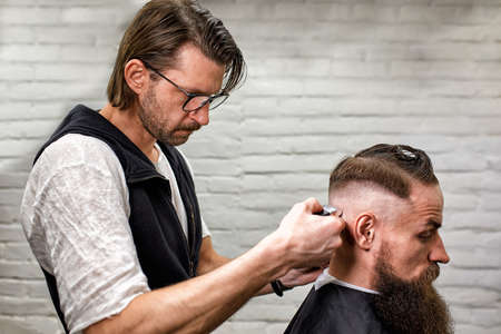 Brutal guy in modern Barber Shop. Hairdresser makes hairstyle a man with a long beard. Master hairdresser does hairstyle with hair clipper