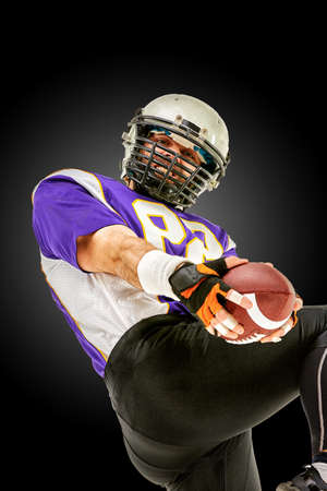 American football player in action with ball Stock Photo