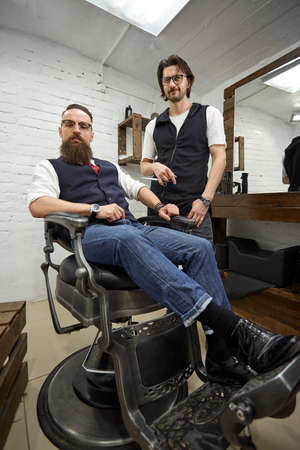Brutal guy in modern Barber Shop. Hairdresser makes hairstyle a man with a long beard. Master hairdresser does hairstyle by scissors and comb Stockfoto