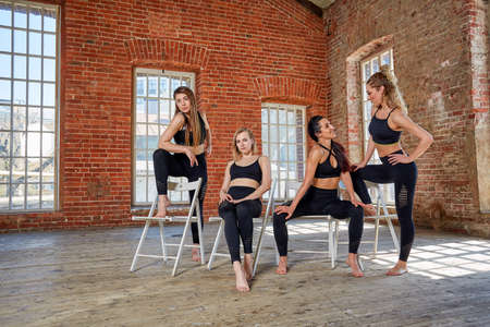 Group portrait of young sporty excited beautiful girls with exercise mats standing beside white wall laughing and talking together. Candid funny students waiting for class to start. Full length photo