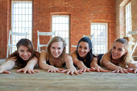 Group portrait of young sporty excited beautiful girls with exercise mats standing beside white wall laughing and talking together. Candid funny students waiting for class to start. Full length photo,