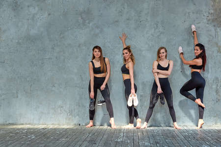 Group portrait of young sporty excited beautiful girls with exercise mats standing beside white wall laughing and talking together. Candid funny students waiting for class to start. Full length photo. Reklamní fotografie