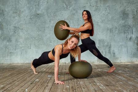 Two young, beautiful fitness girls in the gym posing with fitness balls against a gray wall