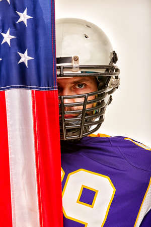 Portrait of an american football player on half closed by american flag. Close-up, white background.