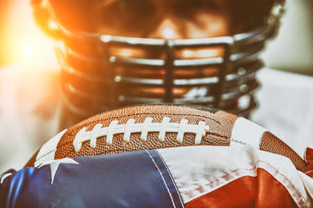 American football concept. The ball for the American football lies on the flag of America against the background of the portrait of the American football player. Stockfoto
