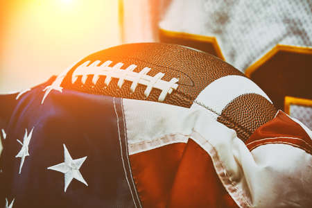 American football concept. The ball for American football lies on the flag of America against the backdrop of an American football player.