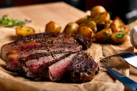 Tasty and fresh, very juicy Ribeye steak from marbled beef on a wooden table with baby potatoes
