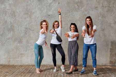 group of young girls are posing against the wall smiling and showing gestures with their hands. Gray background, save space. 版權商用圖片
