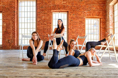 Group of young sports girls resting after a workout in a spacious loft studio. Female friendship in the gym, relaxing after fitness, indoors, sun glare effect.