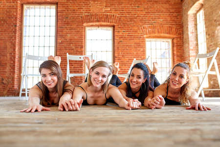 Group portrait of young sporty excited beautiful girls with exercise mats standing beside white wall laughing and talking together.
