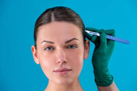 Porträt einer schönen Mädchennahaufnahme, mit glatter Haut, Hände, die ein Skalpell im Gesicht mit Handschuhen halten. Konzeptschönheit, Jugenderhaltung, plastische Chirurgie, Gesundheit. Standard-Bild