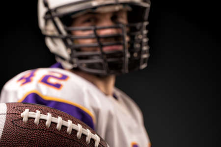 American football player holding the ball in his hands in front of the camera. Concept American football, motivation, black background Stockfoto