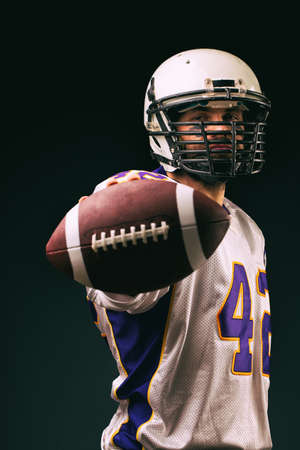 American football player holding the ball in his hands in front of the camera. Concept American football, motivation, black background Stock Photo