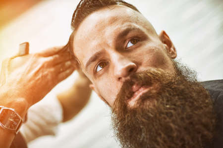Stylish barber cuts a brutal man with a thick beard. Banco de Imagens