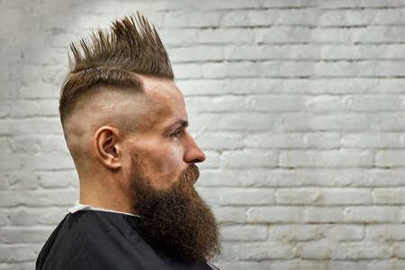 Retrato de un hombre con cresta y barba en un sillón de peluquero contra una pared de ladrillos. de cerca, fondo de ladrillo, espacio de copia