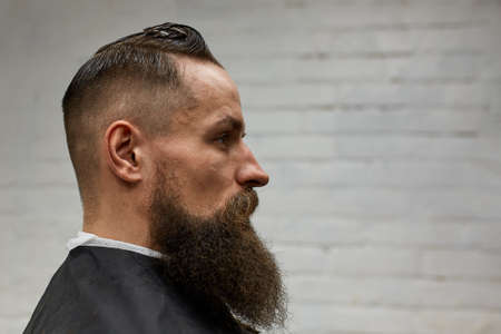 Portrait of a serious man in a barber shop. A man sits in the barbers chair. Copy space on brick wall background.