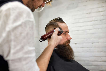 Master Barber does hairstyle and styling. Concept Barbershop. Beard styling and cut. styling of black beard. So trendy and stylish. Advertising and barber shop concept