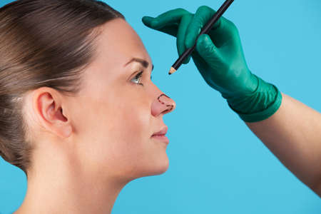 Beautician draw correction lines on woman face. Before plastic surgery operetion. Isolated on blue