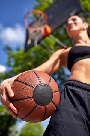Beautiful sexy fitness girl in black sport wear with perfect body with basket ball at basketball court. Sport, fitness, lifestyle concept 스톡 콘텐츠