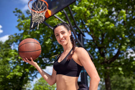 Beautiful sexy fitness girl in black sport wear with perfect body with basket ball at basketball court. Sport, fitness, lifestyle concept Standard-Bild - 122694108