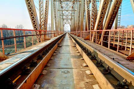 Reliable railway bridge, against the backdrop of beautiful nature and blue sky. Looking through the bridge. Backgound Banco de Imagens - 122694151