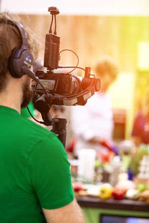 Videofilmer, der einen Film oder eine Fernsehsendung in einem Studio mit einer professionellen Kamera hinter der Bühne dreht Standard-Bild