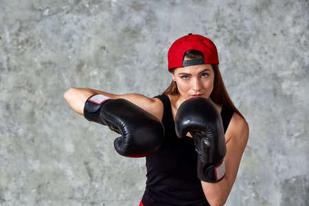 Beautiful athletic girl posing in pink boxing gloves on a gray background. Copy space, close-up. Concept sport, fight, goal achievement. Stock Photo