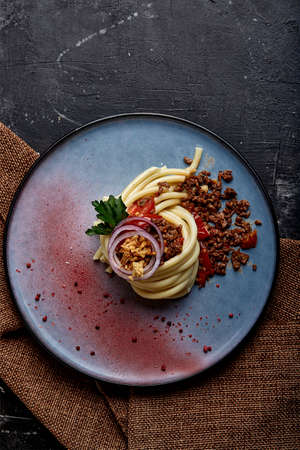 Spaghetti bolognese. Concept Italian cuisine, Spaghetti beautifully laid out on a plate and watered with Bolognese meat sauce. Blue plate, dark background.