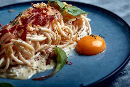 Classic pasta carbonara with yolk on a plate. Pasta laid out on a blue plate on a dark background. Concept of Italian cuisine, beautiful serving dishes, close-up.
