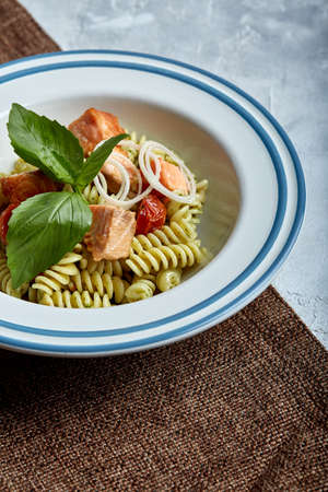 Fusilli pasta with baked salmon and spinach. The concept of Italian cuisine, classic. Beautifully canned table with pasta.