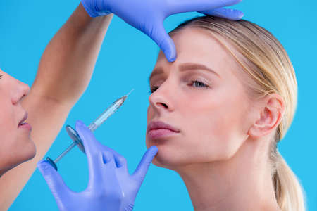 face of a girl with smooth skin without wrinkles makes beauty shots. Syringe next to the face, skin care salon. Gloved hands. closeup portrait. Skin care beauty concept, surgery, youth. 写真素材 - 124754173