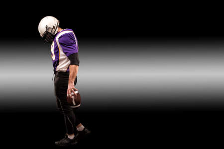 American football player holding ball in his hands in smoke. Black background, copy space. The concept of American football, motivation, copy space